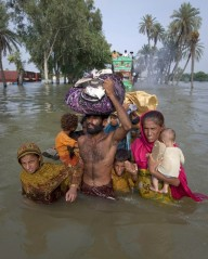 A family wades through flood waters in Pakistan's Muzaffargarh district of Punjab province
